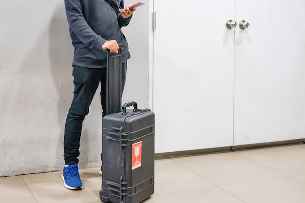 Młody człowiek używa smartphones z jego bagażem sprawdzać przy lotniskami lot
