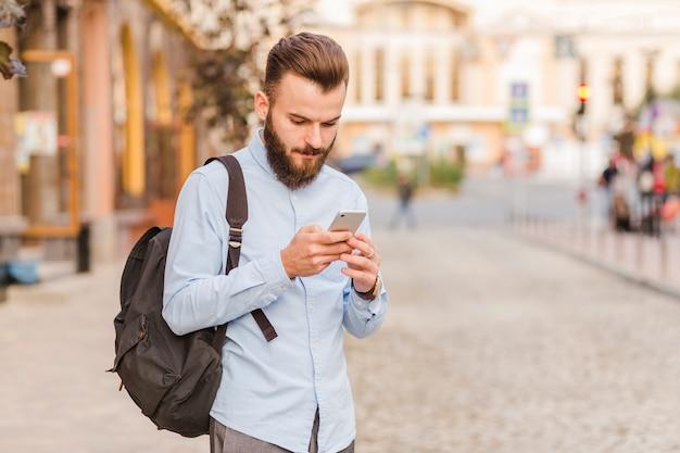 Młody człowiek używa telefon komórkowego przy outdoors