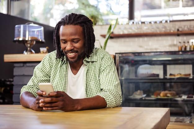 Młody człowiek używa telefon komórkowego w bufecie