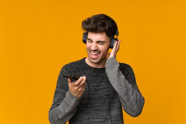 Młody człowiek używa telefon komórkowego z hełmofonami i śpiewem