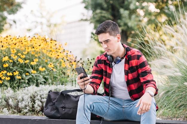 Młody człowiek używa telefon komórkowego