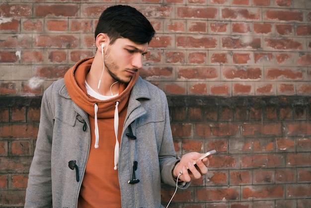 Młody człowiek używa telefon komórkowego.