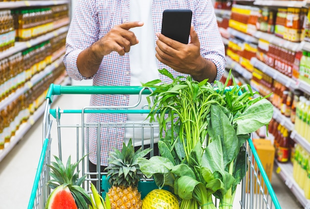 Młody człowiek używa telefon podczas gdy robiący zakupy przy supermarketem.