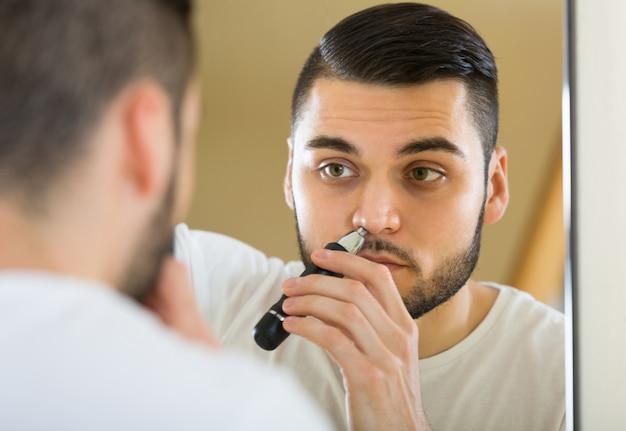 Młody człowiek używa włosianą drobiażdżarkę