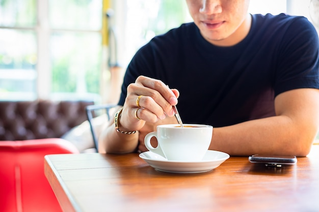 Młody człowiek używać małej łyżeczki w filiżance kawy