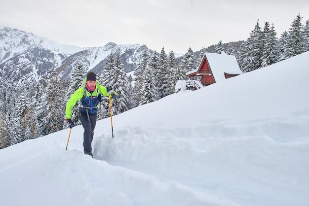 Młody człowiek w akcji na nartach wspinaczkowych