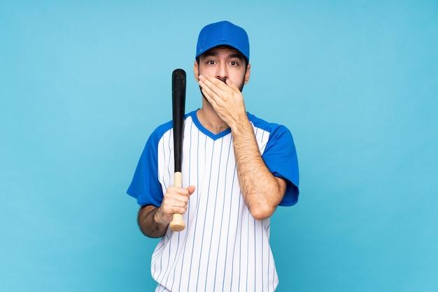 Młody człowiek w baseball nad niebieskim obejmującego usta rękami