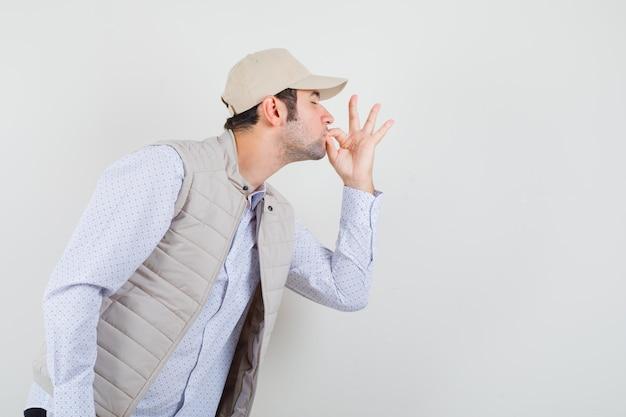 Młody człowiek w beżowej kurtce i czapce pokazuje pyszny gest i wygląda na szczęśliwego, widok z przodu.