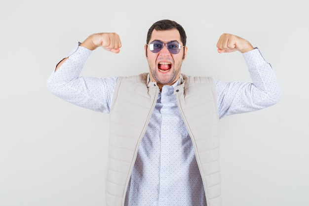Młody człowiek w beżowej kurtce i czapce zakłada okulary, pokazując pozę zwycięzcy, wystawiający język i optymistycznie wyglądający widok z przodu.