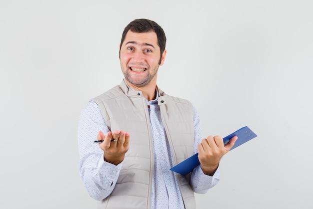Młody człowiek w beżowej kurtce podnosząc rękę w pytający sposób, trzymając notatnik i długopis i patrząc optymistycznie, widok z przodu.