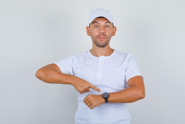 Młody człowiek w białej koszulce, czapce pokazuje zegarek z palcem wskazującym i wygląda podekscytowany, widok z przodu.