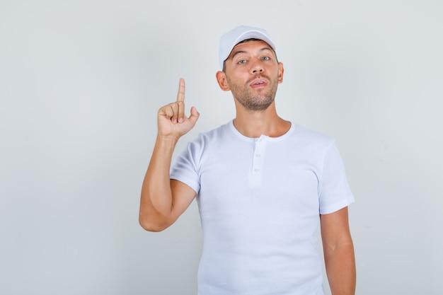Młody człowiek w białej koszulce, czapka skierowana w górę palcem wskazującym i pewny, widok z przodu.