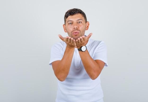 Młody człowiek w białej koszulce dmuchanie pocałunek rękami i patrząc pozytywnie, widok z przodu.