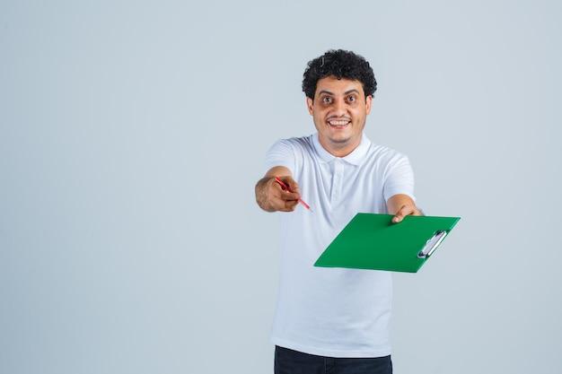 Młody człowiek w białej koszulce i dżinsach przedstawia notatnik i pióro do kamery i wygląda na szczęśliwego, przedni widok.