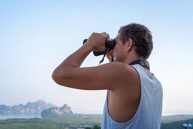 Młody człowiek w białej koszulce patrzy przez lornetkę z góry na tło nieba i skał.