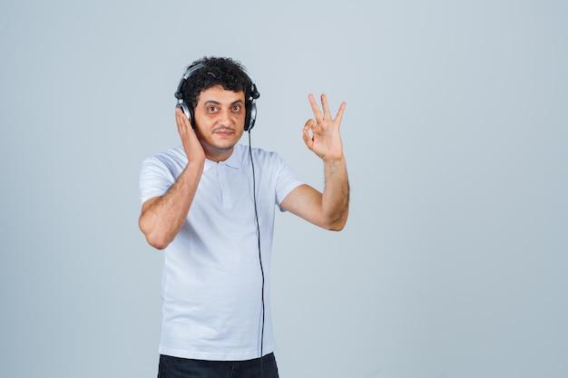 Młody człowiek w białej koszulce pokazujący ok gest podczas słuchania muzyki i wyglądający pewnie, widok z przodu.