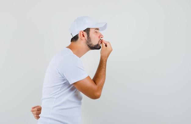 Młody człowiek w białej koszulce pokazuje pyszny gest i wygląda skoncentrowany, widok z przodu.