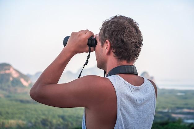 Młody człowiek w białej koszulce spogląda z góry w dal przez lornetkę na przyrodę.