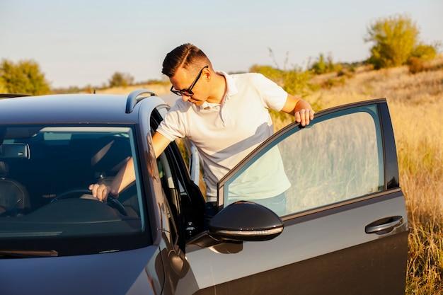 Młody człowiek w białej koszulce trzyma kierownicę
