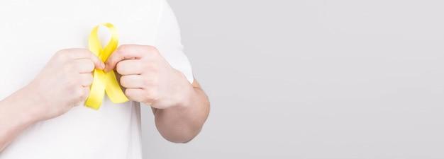 Młody człowiek w białej koszulce z żółtą wstążką symbol świadomości samobójstwa, mięsaka raka kości, raka pęcherza moczowego, raka wątroby i koncepcji raka wieku dziecięcego. opieka zdrowotna. copyspace.