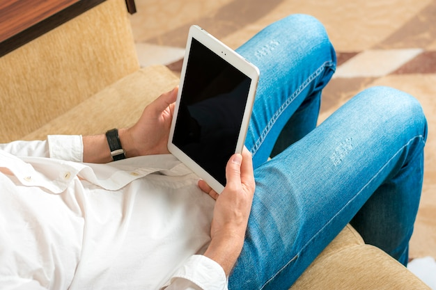 Młody człowiek w białej koszuli i niebieskich dżinsach pracuje i patrzeje na pastylce z czarnym ekranem w domowym biurze na wygodnej beżowej kanapie