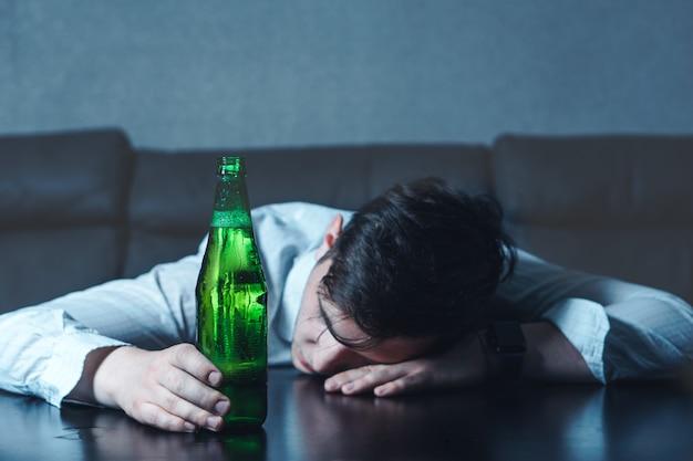 Młody człowiek w białej koszuli śpi na stole z zieloną butelką piwa