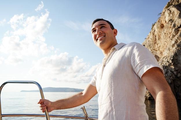 Młody człowiek w białej koszuli stojący na jachcie nosowym na morzu
