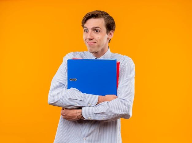 Młody człowiek w białej koszuli trzymając foldery patrząc na bok z nieśmiałym uśmiechem na twarzy stojącej na pomarańczowym tle