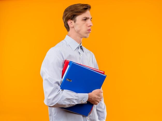 Młody człowiek w białej koszuli trzymając foldery patrząc na bok z poważną miną niezadowolony stojąc na pomarańczowym tle