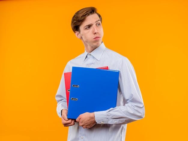 Młody człowiek w białej koszuli trzymając foldery patrząc na bok z poważną twarzą stojącą na pomarańczowym tle
