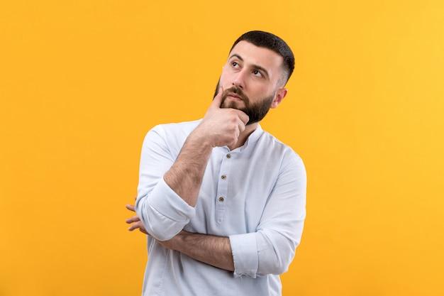 Młody człowiek w białej koszuli z brodą myślenia wyrażenie