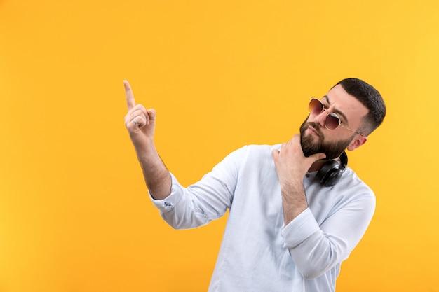 Młody człowiek w białej koszuli z brodą, okulary przeciwsłoneczne i czarne słuchawki