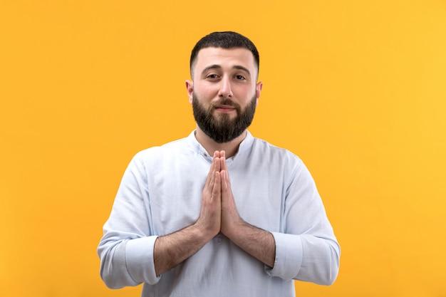 Młody człowiek w białej koszuli z brodą w modlitwie stanowią