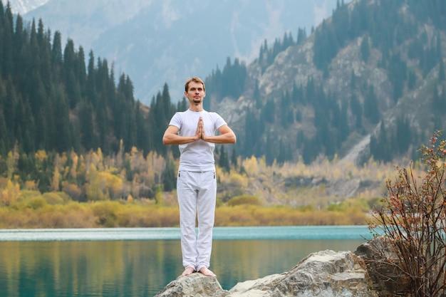 Młody człowiek w białych ubraniach ćwiczy jogę w górach. ustaw samasthiti namaskar.