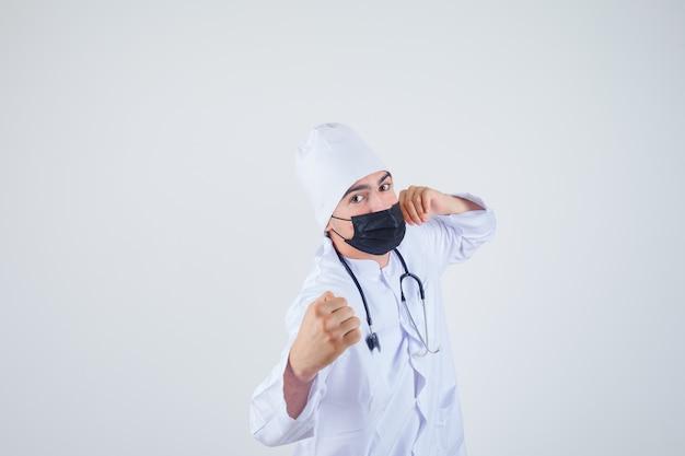 Młody człowiek w białym mundurze, maska stojąca w pozie walki i wyglądający pewnie, widok z przodu.
