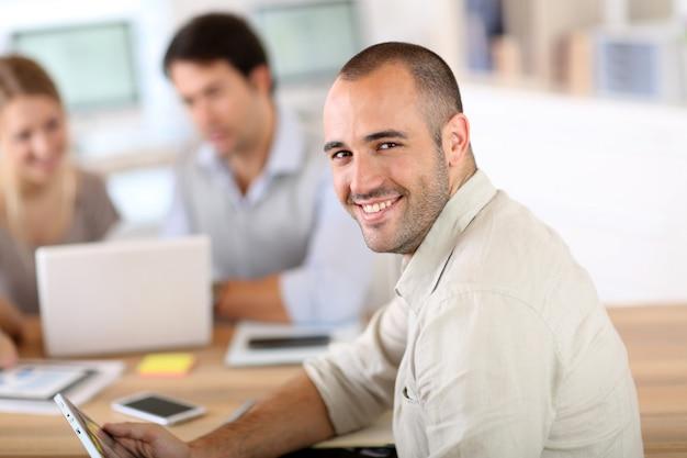 Młody człowiek w biurze pracuje na cyfrowej pastylce