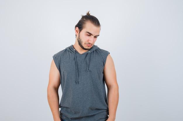 Młody człowiek w bluzie bez rękawów, patrząc w dół i spuszczony, widok z przodu.