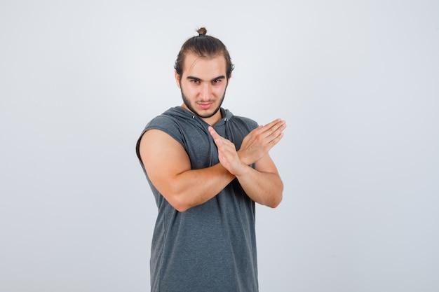 Młody człowiek w bluzie z kapturem, pokazując gest stop, stojąc bokiem i wyglądając atrakcyjnie.