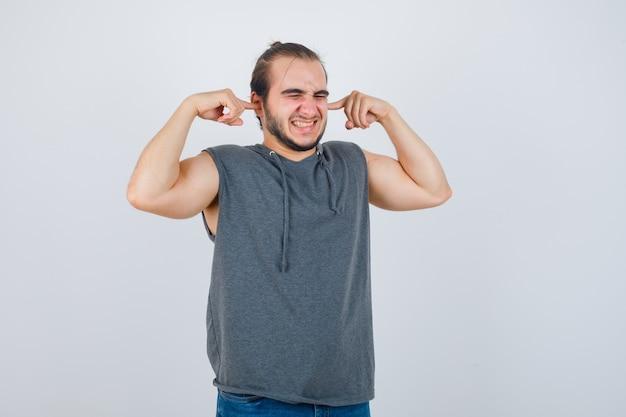 Młody człowiek w bluzie z kapturem, trzymając palce na uszach i niezadowolony, widok z przodu.