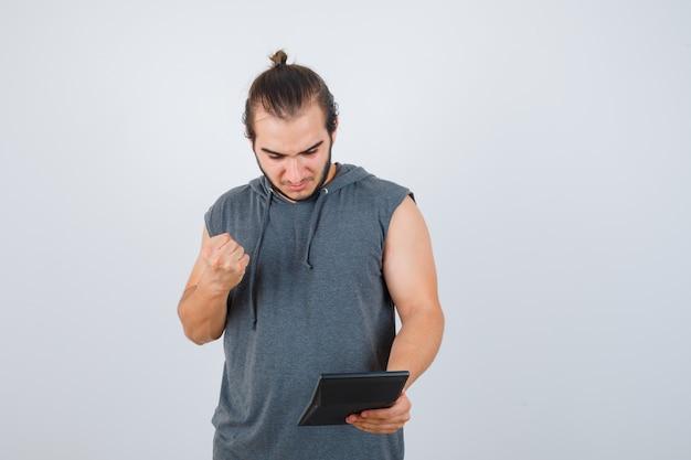 Młody człowiek w bluzie z kapturem, trzymając pięść w pobliżu klatki piersiowej i patrząc tęsknie z przodu.
