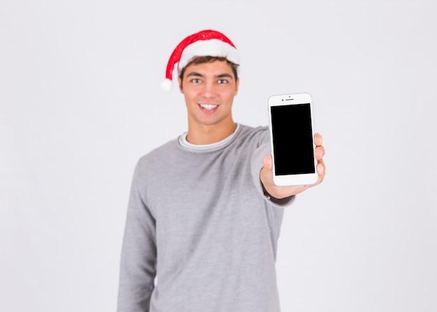 Młody człowiek w bożenarodzeniowym kapeluszu pokazuje smartphone