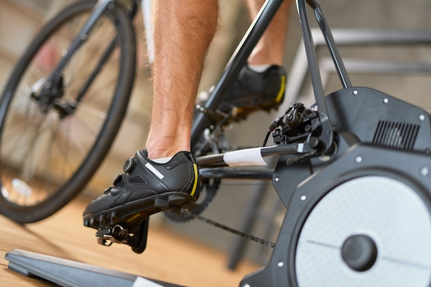 Młody człowiek w butach sportowych jeździ na rowerze stacjonarnym