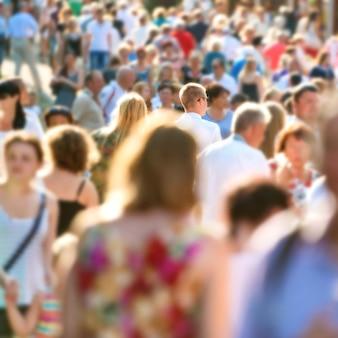 Młody człowiek w centrum tłumu ludzi chodzących na ruchliwej ulicy miasta.
