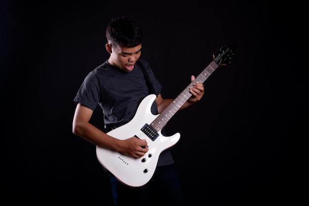Młody człowiek w ciemnej koszulce z gitarą elektryczną