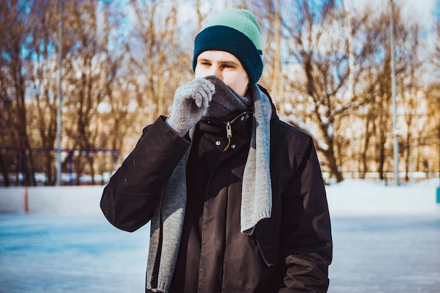 Młody człowiek w ciepłe ubrania i szalik na zimowy dzień