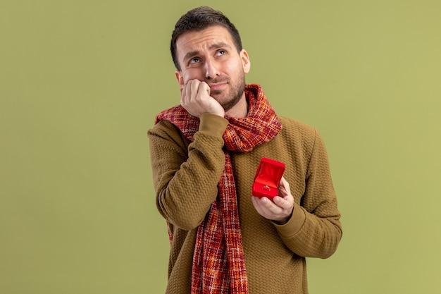 Młody człowiek w codziennych ubraniach z szalikiem na szyi trzymający czerwone pudełko z pierścionkiem zaręczynowym patrząc zmartwiony koncepcja walentynek stojących nad zieloną ścianą
