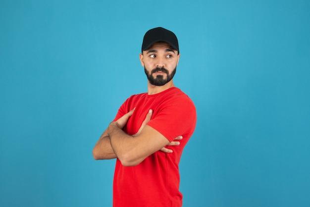 Młody człowiek w czapce na sobie czerwony t-shirt stojący ze skrzyżowanymi rękami.