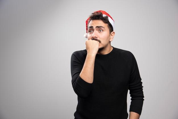Młody człowiek w czapce świętego mikołaja boi się czegoś.