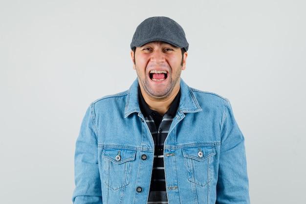 Młody człowiek w czapkę, t-shirt, kurtkę, patrząc na kamery, śmiejąc się