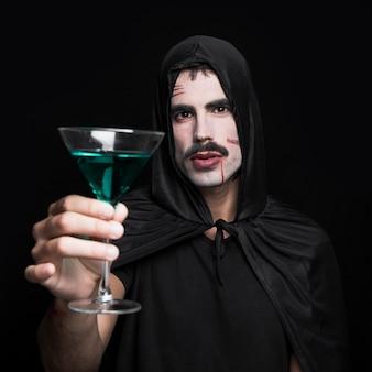 Młody człowiek w czarnej halloweenowej pelerynie z kapiszonem pozuje w studiu z zielonym napojem